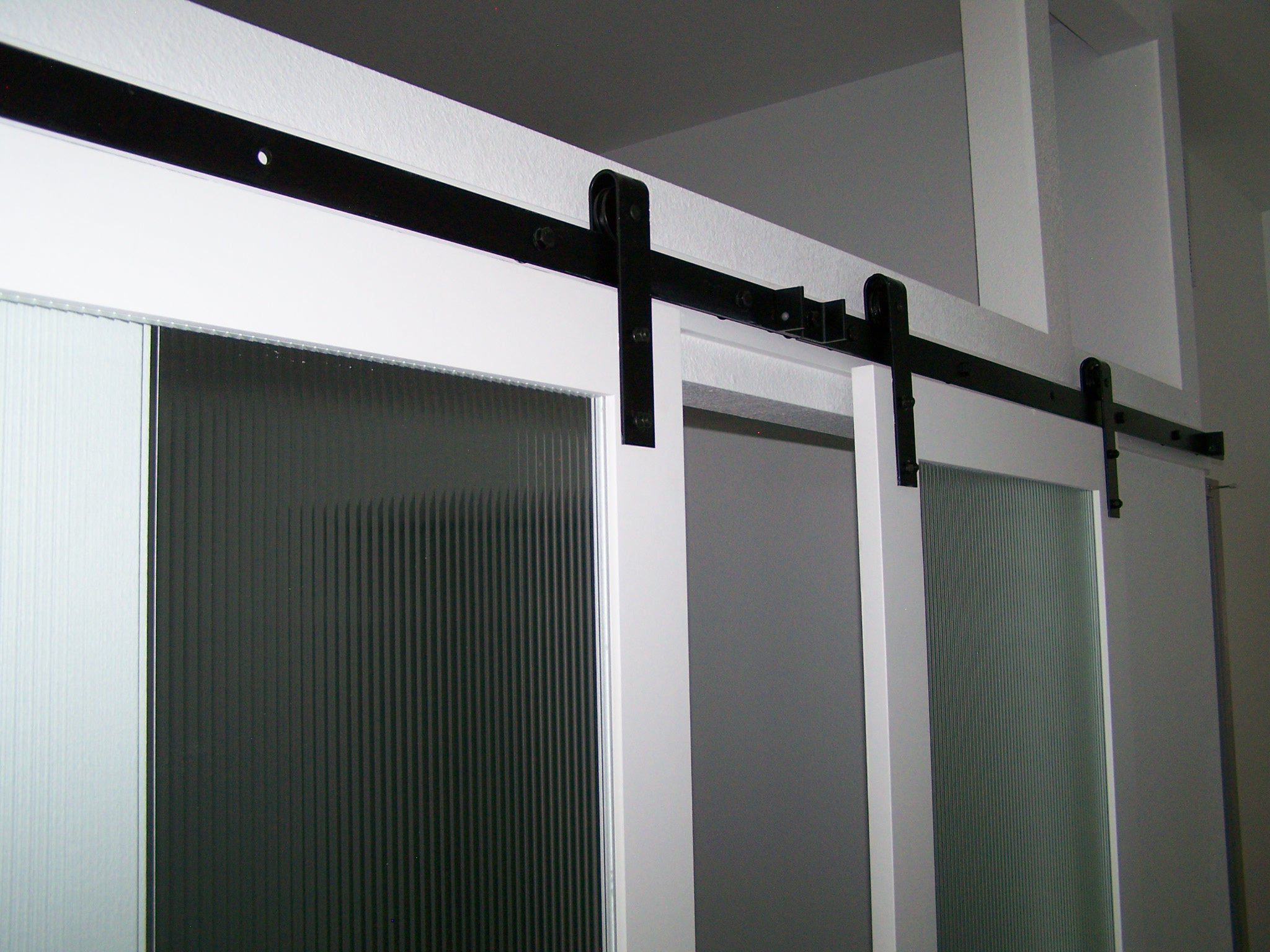 Close-up view of Goldberg Brothers barn door hardware on double door entry
