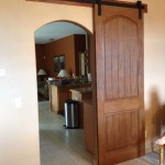 The matching arched barn door compliments the entry opening, and is paired with Goldberg Brothers barn door hardware.