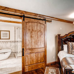 A unique wooden barn door in master suite, using Goldberg Brothers Barn Door hardware.